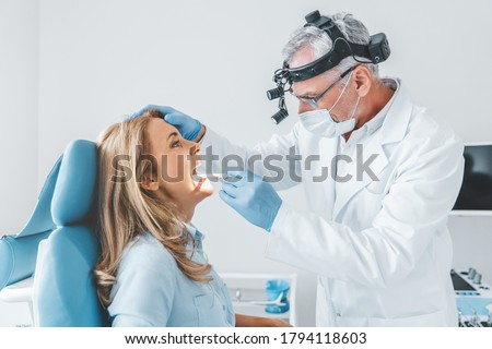 Experienced doctor examines adult woman for sore throat Royalty-Free Stock Photo #1794118603