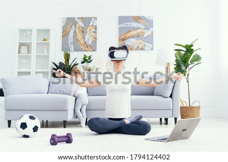 Young pretty mom meditating in lotus yoga position using virtual reality goggles while her daughter watches cartoons at home on background.
