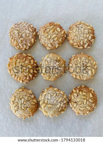 Pictured here is pignoli or pine nut cookies. It is three by three rows of pine nut cookies. Pine nut cookies are almond batter rolled in pine nuts, baked and dusted with powdered sugar.