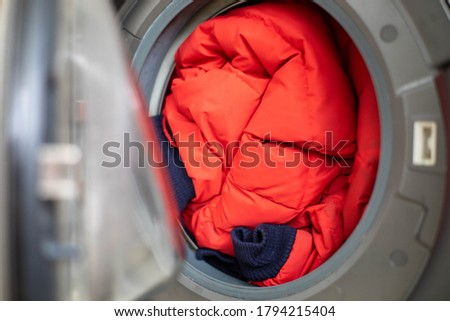 Open door in washing machine with dirty down jacket inside, close up, preparation for cleaning, copy space Royalty-Free Stock Photo #1794215404