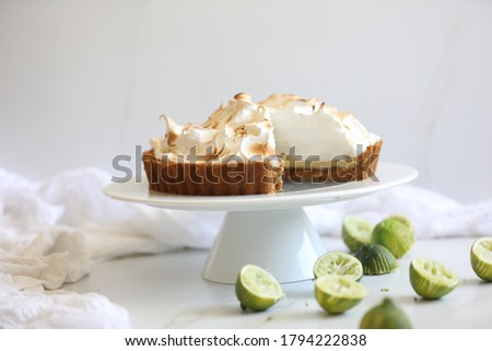 Classic Key lime pie topped with  meringue against white background, Traditional American dessert tart made of Key lime juice, egg yolks & sweetened condensed milk. Summer citrus fruit dessert concept
