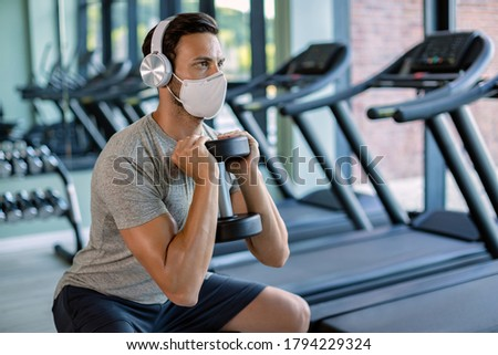Male athlete using hand weight while doing squats and wearing protective face mask in health club.  #1794229324