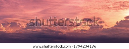 Panorama view red and purple sunset sky. Beautiful cloudscape in heaven sky. Nature background. Golden and dark fluffy clouds with sunlight. Beautiful clouds layer. Majestic sky for wallpaper.  Royalty-Free Stock Photo #1794234196