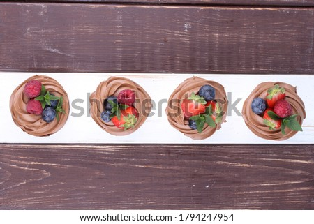 Cupcakes with whipped chocolate and berry, on wooden table. Picture for a menu or a confectionery catalog. Top view.