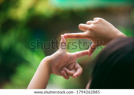A little girl is making her hand gestures a camera symbol to aim at a target like she is actually using a camera.