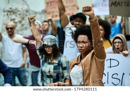 African American woman with raised fist participating in black civil rights demonstrations.  Royalty-Free Stock Photo #1794280111
