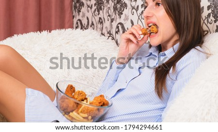 Young happy woman eating deep fried chicken, closeup. Woman eats chicken wings, calorie intake and health risks, cholesterol.