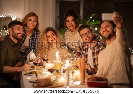 holidays, celebration and people concept - happy friends taking selfie by smartphone at home christmas dinner party