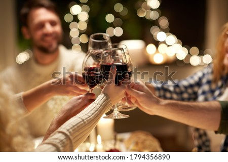 holidays, celebration and people concept - happy friends having christmas dinner at home drinking non-alcoholic red wine #1794356890