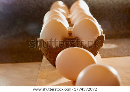White chicken eggs in cardboard on wooden surface with interesting light. The concept of taking pictures of food. Fresh eggs from the farm. Organic egg production. Chicken egg industry. Eggs for sale