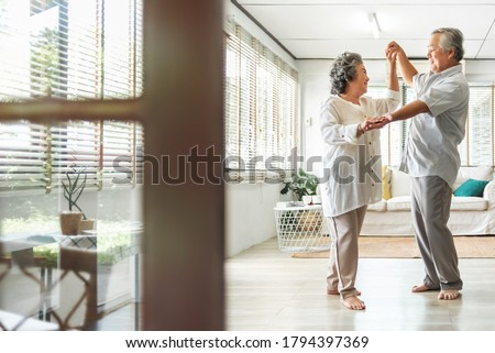 Romantic Asian Senior couple dancing at home. Happy Smiling Grandfather and Grandmother having fun Celebrating in wedding Anniversary day. Elderly man and woman holding hands together, Romance, lover #1794397369