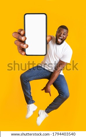 New awesome mobile app. Closeup of smartphone with blank screen in jumping emotional black guy hand, yellow studio background #1794403540