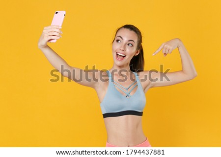 Excited fitness sporty woman in sportswear working out isolated on yellow background. Workout sport motivation lifestyle concept. Doing selfie shot on mobile phone, pointing index finger on herself