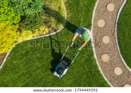 Caucasian Gardener Mowing Backyard Garden Grass Using Cordless Electric Grass Mower. Aerial View. Gardening and Landscaping Industry. #1794449392