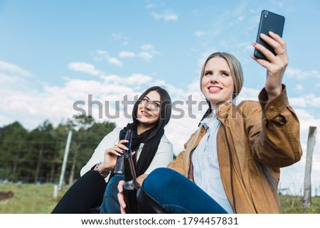 Two women take a picture.  They taking selfie portrait while sitting outdoors.  They drink beer and enjoy.