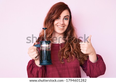 Young beautiful woman holding french coffee maker smiling happy and positive, thumb up doing excellent and approval sign