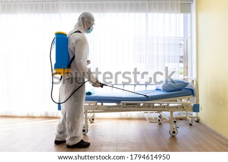Staff protective suit PPE and mask.Cleaning and Disinfection in a room of hospital amid the coronavirus epidemic Professional teams for disinfection efforts Infection prevention control of epidemic. Royalty-Free Stock Photo #1794614950