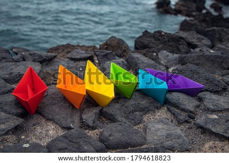Colored paper boats with the colors of the rainbow in front of the ocean