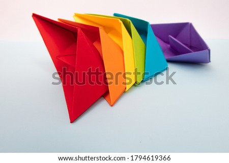 Colored paper boats with the colors of the rainbow on a light blue background