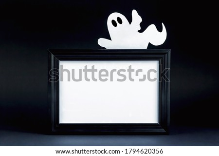 Background for Halloween. Black frame with free space on a black background. A white ghost figure peeks out from behind an empty black photo frame. Halloween typography concept. Halloween Ideas.