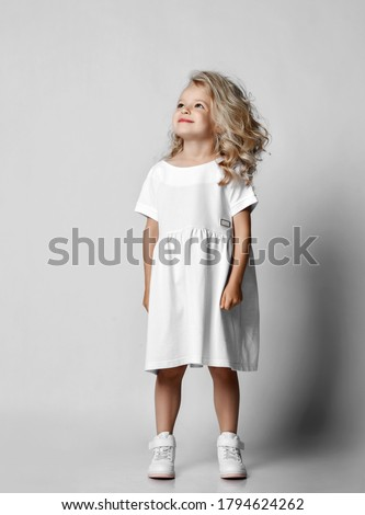 Smiling positive little blonde curly kid girl in white casual dress and sneakers is looking at copy space at upper corner. Stylish comfortable everyday fashion for children concept Royalty-Free Stock Photo #1794624262