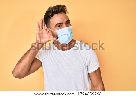 Young hispanic man wearing medical mask smiling with hand over ear listening and hearing to rumor or gossip. deafness concept.  #1794656266