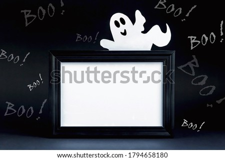 Background for Halloween. Black frame with free space on a black background with lots of BOO! A white ghostly figure peeks out from behind an empty black photo frame. Halloween ideas, concept.