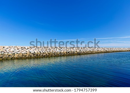 A massive stone wall constructed in the sea, used as a breakwater, and built to enclose or protect an anchorage or a harbor Royalty-Free Stock Photo #1794757399