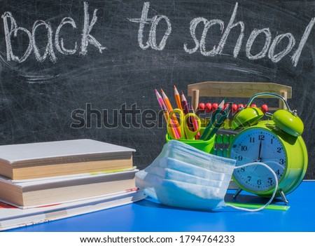 "School supplies, alarm clock, books and  medical mask on the school desk against the background of the blackboard with the words ""back to school"" Concept for a new learning environment in the COVID-19 Royalty-Free Stock Photo #1794764233"