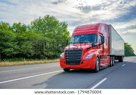 Heavy loaded classic red big rig semi truck with high roof transporting commercial cargo at dry van semi trailer running on the straight wide divided multiline highway road for timely delivery #1794870004