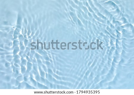 Blurred transparent blue colored clear calm water surface texture with splashes and bubbles. Trendy abstract nature background. Water waves in sunlight. Royalty-Free Stock Photo #1794935395