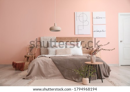 Interior of beautiful modern bedroom with spring flowers Royalty-Free Stock Photo #1794968194