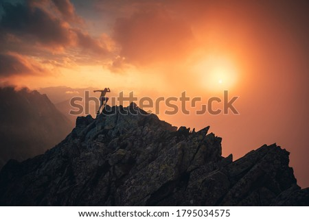 Sport photo in mountains. Silhouette of runner on the top of the hill, orange sunset sky in background. Edit space