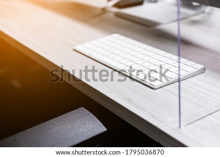 Wireless keyboard with acrylic plexiglass separator setting on the work station desk. New normal Concept for social distancing in offices during the Covid-19 pandemic. Precaution and safe. #1795036870