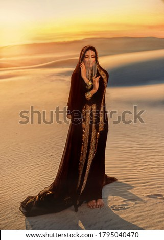 woman in black long dress stands in desert. Luxurious clothes, gold veil accessories hide face. Oriental beauty fashion model. Sand dunes background yellow orange sunset. abaya dress, hijab headscarf Royalty-Free Stock Photo #1795040470