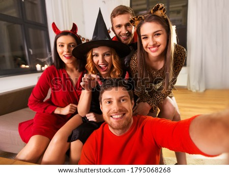 friendship, holiday and people concept - group of happy smiling friends in halloween costumes of vampire, devil, witch and cheetah taking selfie at home party at night