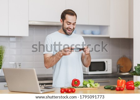 Funny young bearded man in white t-shirt taking food pictures on mobile phone preparing vegetable salad cooking food in light kitchen at home. Dieting healthy lifestyle concept.