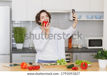 Funny young housewife woman in casual clothes preparing vegetable salad cooking food in light kitchen at home. Dieting healthy lifestyle concept. Doing selfie shot on mobile phone, biting bell pepper