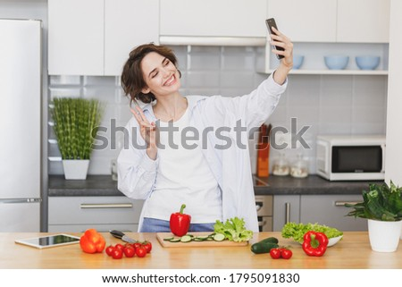 Smiling housewife woman in casual clothes preparing vegetable salad cooking food in light kitchen at home. Dieting healthy lifestyle concept. Doing selfie shot on mobile phone, showing victory sign