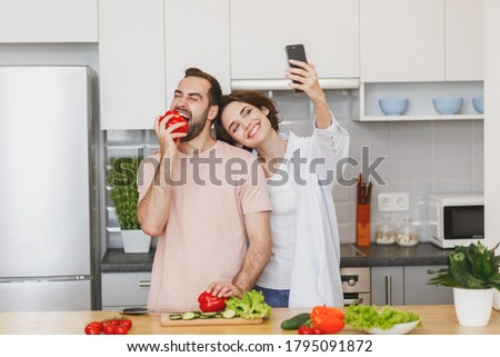 Funny young couple friends guy girl preparing vegetable salad cooking food in light kitchen at home. Dieting family healthy lifestyle concept. Doing selfie shot on mobile phone, biting bell pepper