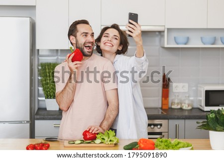 Excited young couple friends guy girl preparing vegetable salad cooking food in light kitchen at home. Dieting family healthy lifestyle concept. Mock up copy space. Doing selfie shot on mobile phone