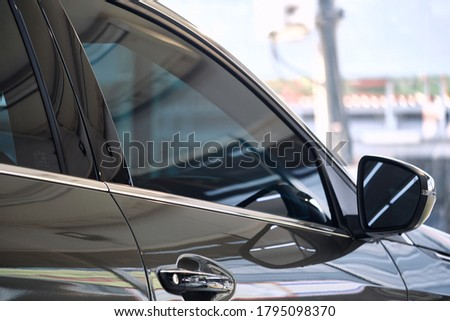 Side view of car window tint. Ceramic film provide heat rejection & UV protection with color stable shade. Automobile film installed to glass surface of red car. Car tinting service. Selective focus. #1795098370