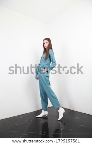 Side view of a Caucasian teenage model posing in blue summer suit in a studio with white walls background. Fashion industry campaign, catalog photosession for online store