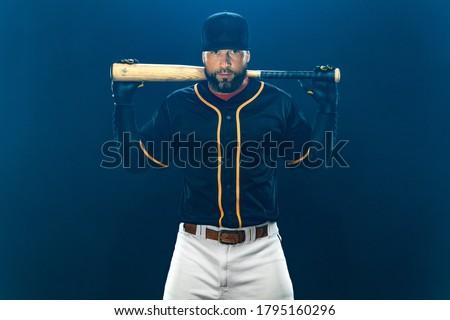 Baseball player with bat on dark background. Ballplayer portrait. Royalty-Free Stock Photo #1795160296