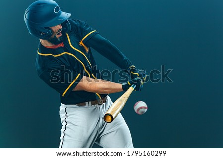Baseball player with bat taking a swing on grand arena. Ballplayer on dark background in action. Royalty-Free Stock Photo #1795160299