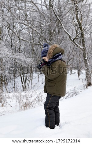 a boy in warm clothes walks in the winter forest and takes pictures of nature, trees and shrubs in the snow after winter snowfalls, in the hands of a child boy black camera, closeup