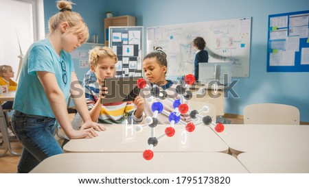 Three Diverse School Children in Chemistry Science Class Use Digital Tablet Computer with Augmented Reality Application, Looking at Educational 3D Animation of a Molecule. VFX, Special Effects Render