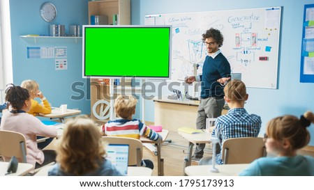 Elementary School Physics Teacher Uses Interactive Digital Whiteboard With Green Screen Mock-up Template. He Leads Lesson to Classroom full of Smart Diverse Children. Science Class with Kids Listening