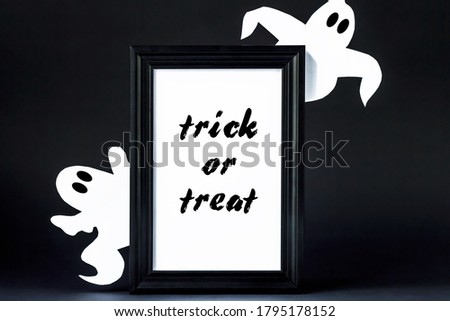 "Background for Halloween. Black frame with the words ""Trick or treat"" on a black background. A white ghostly figure peeps out from behind the black lettering. Halloween typography concept and ideas."