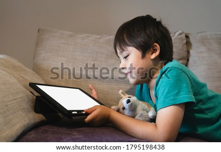 Cropped shot kid lying on sofa watching cartoons on tablet,6-7 year old boy playing game on touch pad, Children having activity on his own with mock up of digital tablet.New normal  education